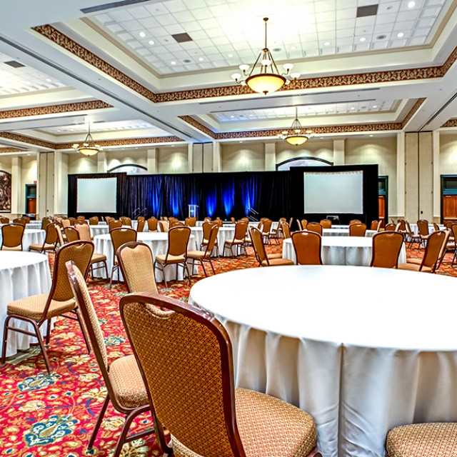 Image of entire Grand Ballroom set in crescent rounds with a stage, podium and two projection screens.