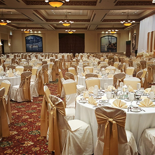 Image of Grand Ballroom set for a wedding with banquet tables, white chair covers, gold sashes and white drape.