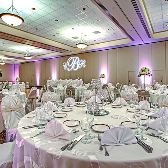 Image of the Junior Ballroom set for a wedding with banquet tables, white table cloths and chair covers, a dance floor, monogram GOBO, and uplighting.
